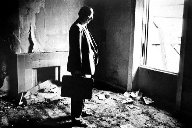 Gerry Fitt standing in his burned out home